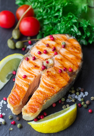 prepared fish: grilled salmon steak with pink pepper and lemon