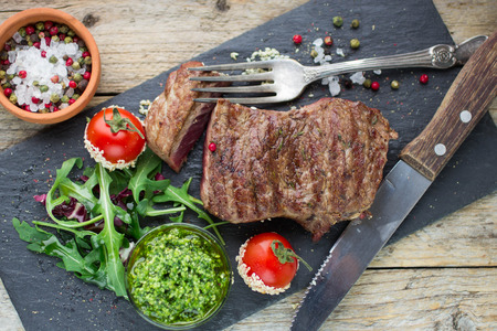 Beef steak grilled with tomatoes, arugula and pesto on black plate Stockfoto