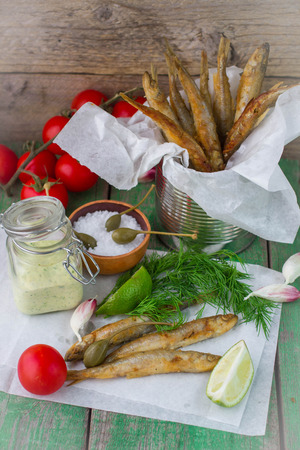 smelt: Fried small fish. Fried smelt on the table with a sauce, lime, tomatoes, dill and garlic