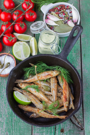 smelt: Fried small fish. Fried smelt in the pan on the table with a sauce, lime, tomatoes, dill and garlic