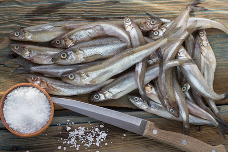 smelt: Freshly caught small fish. Smelt on a wooden surface