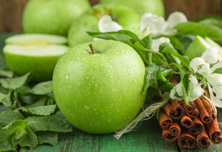 Green apples, mint and cinnamon on wooden table Stockfoto