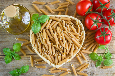 wholemeal pasta. pasta from whole wheat flour, tomatoes and Basil on wooden table