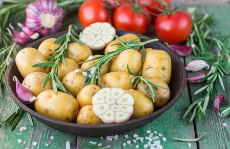 Potatoes for roasting with rosemary, garlic, olive oil and coarse sea salt Stock Photo