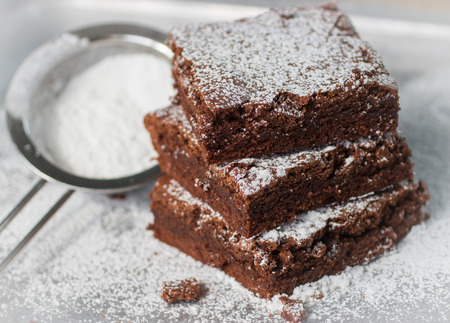chocolate powder: Brownie. Chocolate cakes with powdered sugar  on a metal baking sheet.  American dish. Selective focus