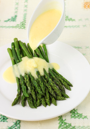 freshly cooked: freshly cooked green asparagus with hollandaise sauce. Selective focus