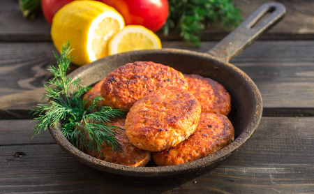 salmon fishcakes in a cast iron skillet, tomatoes and lemon on a dark table. Selective focus Stock Photo