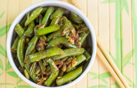 oriental cuisine: Green beans with garlic, onion and red pepper. Warm salad. The garnish. Dish Oriental cuisine. Selective focus