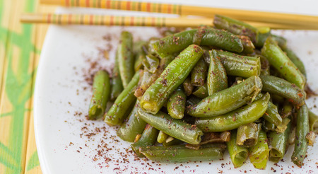 ejotes: Judías verdes con ajo, la cebolla y el pimiento rojo. Ensalada templada. La guarnición. Cocina oriental plato. Enfoque selectivo