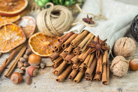 christmas scent: Cinnamon sticks, star anise and nuts on an old wooden table. New year and Christmas compositions. Selective focus