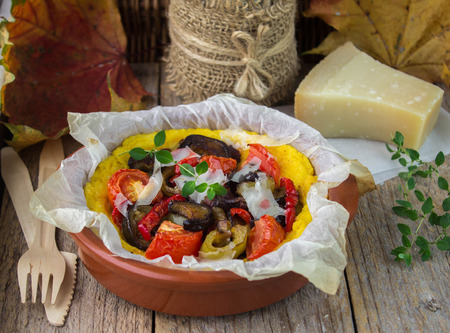 Baked polenta with tomatoes, eggplant, bell pepper and thyme. Selective focus