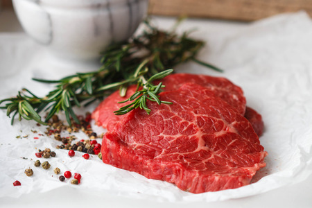 white meat: Raw fresh steaks from the marble beef, rosemary and spices on the table. Selective focus