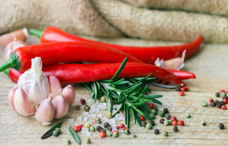 mediterranean cuisine: Ingredients of Mediterranean cuisine - garlic, pepper, rosemary and spices on old wooden table Stock Photo