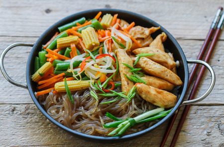 oriental cuisine: Glass noodles with chicken, green beans, carrots, corn, soya sprouts and greens. Oriental cuisine Stock Photo