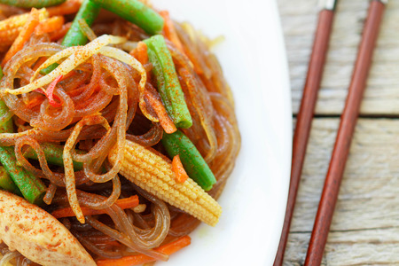 oriental cuisine: Spicy glass noodles with chicken, green beans, carrots, corn and soy sprouts. Oriental cuisine