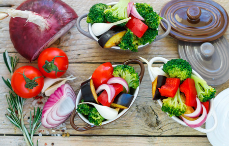 Raw fresh vegetables - broccoli, eggplant, peppers, tomatoes, onions, garlic in portion pots. Preparation of the garnish