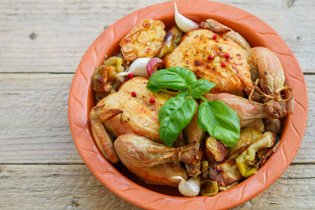 whole chicken: Two small whole chicken baked with onions, apples, garlic and spices in a clay form Stock Photo