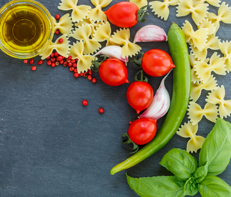 italian cuisine: Ingredients for cooking Italian cuisine - pasta, tomatoes, garlic, Basil, hot pepper, olive oil and spices. Top view . Copy space Stock Photo