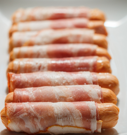 ready to cook food: Sausages wrapped in bacon ready for roasting