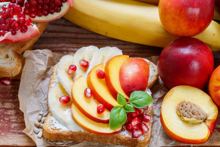 Healthy Breakfast. Dessert. Toast with cream cheese, banana, peach, nectarine and pomegranate