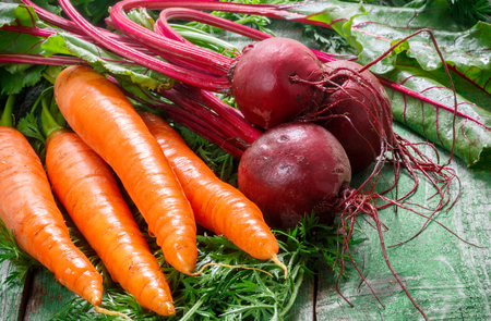 A bunch of young organic carrots and beets with leaves on a wooden table. Vegetables from the garden Stock Photo