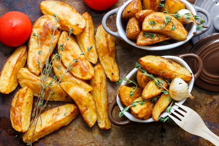 Baked potato wedges with spices, garlic, and thyme on a metal baking sheet and portion pots . Top view
