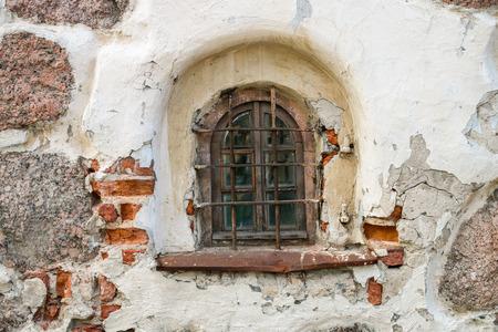 semicircular: A semicircular window with bars in an old brick building