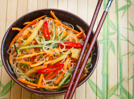 Spicy glass noodles with vegetables - carrots, cucumber, peppers, garlic. Dish  Asian and Oriental cuisine. Selective focus