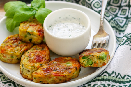 Healthy vegetarian potato patties with carrots, broccoli, bell pepper, green peas and onions with sour cream sauce with dill and Basil. Selective focus Stockfoto