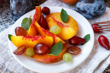 Fruit salad in white plate. Snack of fresh peaches, grapes, dogwood, plums, and mint leaves. Healthy Breakfast. Selective focus