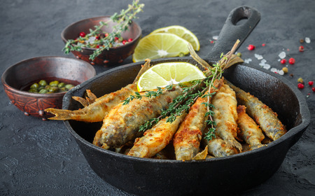 Fried smelt in a frying pan on the table with lemon, thyme, capers, spices and red onion. Small fish Stock Photo