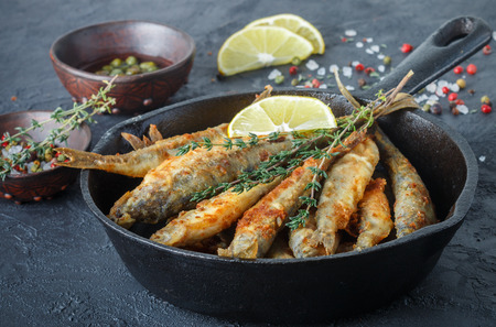 smelt: Fried smelt in a frying pan on the table with lemon, thyme, capers, spices and red onion. Small fish Stock Photo