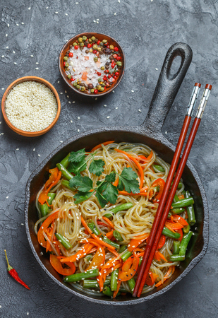 Starch (rice, potato) noodles with vegetables - bell peppers, carrots, green beans, onions, sesame seeds and soy sauce. Vegetarian dish. A delicious dinner in the Asian style Stock Photo