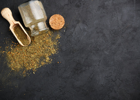 Zaatar - mix of Oriental spices on a dark stone background. Seasoning made from dried herbs, mixed with sesame seeds, sumac, salt and other spices. Top view.  Copy space. Selective focus