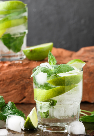 Mojito cocktail or lemonade with lime, mint and ice cubes. Traditional summer refreshing drink. Selective focus