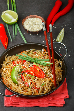 korean salad: Spicy glass noodles with meat and vegetables - beef, carrots, bell peppers, zucchini, lime, chili pepper, ginger, green onions and sesame seeds. Traditional popular dish of Asian cuisine. Selective focus Stock Photo