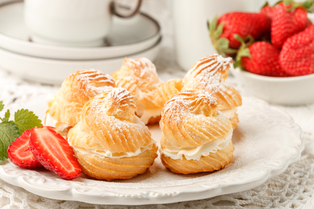 Homemade profiteroles with cream, strawberries and mint. Dessert for gourmets. Selective focus Stock Photo