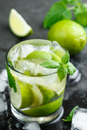 Cold refreshing summer drink with lime, mint and ice cubes in a glass on a dark stone background. Mojito. Lemonade. Detox. Mineral water. Selective focus Stock Photo