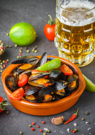Mussels in shells with tomatoes and spicy sauce of chili peppers and garlic. Tasty snack to beer. Mediterranean dishes. Selective focus 免版税图像