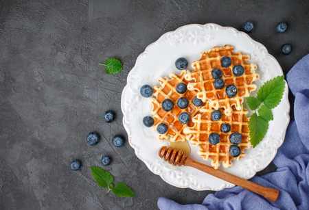 Viennese waffles with honey and fresh berries blueberry and mint on black surface. Delicious dessert. Copy space