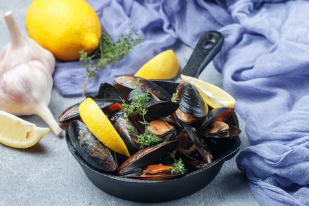 Mussels in the shell with lemon, garlic and thyme. A delicious Mediterranean appetizer made of seafood. Selective focus