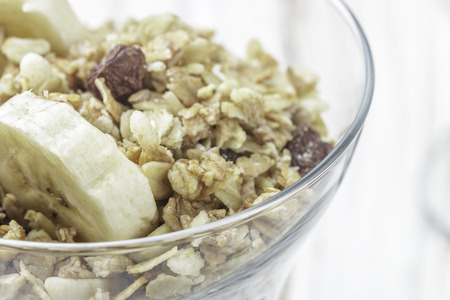 Homemade granola with banana, nuts and raisins closeup. Selective focus Stock Photo