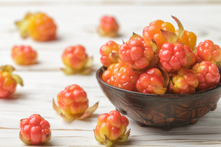 chicouté: Fresh organic Berry cloudberries in a clay bowl on light wooden background. Selective focus