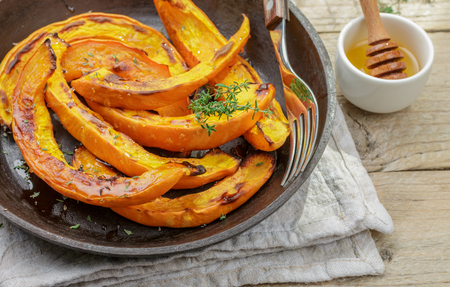 Baked slices of pumpkin with thyme and honey. Healthy dessert for gourmets. Selective focus