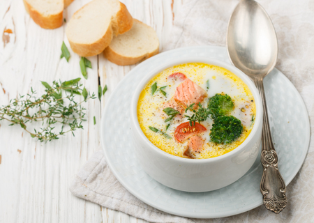 Chowder with salmon, potatoes, carrots, tomatoes and broccoli in a white bowl on bright wooden table Stock Photo