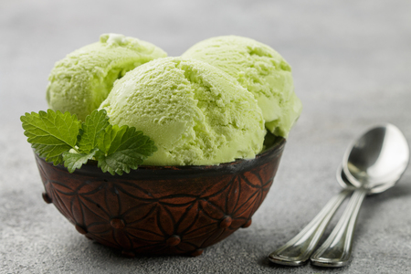 Avocado homemade ice cream with mint leaves on gray concrete background