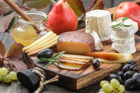 foodies: Set of fine cheeses with fruit and honey. Camembert. Bree. Grapes, pears and rosemary. Wine snacks for foodies. Selective focus Stock Photo