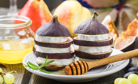 Appetizer of figs and goat cheese with honey. Layered salad of gourmet. Pears, grapes and rosemary on the table. Selective focus Stock Photo