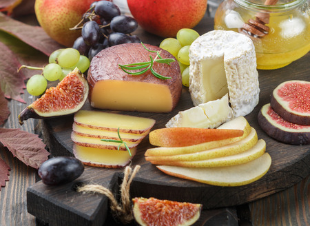 foodies: Set of fine cheeses with fruit and honey. Camembert. Bree. Grapes, figs, pears, and rosemary. Wine snacks for foodies. Selective focus