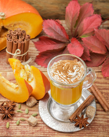Pumpkin spice latte smoothie with whipped cream and cinnamon in glass Cup on wooden background. Traditional autumn hot or cold beverage. Country style. Selective focus